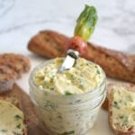 Small glass jar of vegan garlic spread surrounded by baguette slices; butter knife in spread