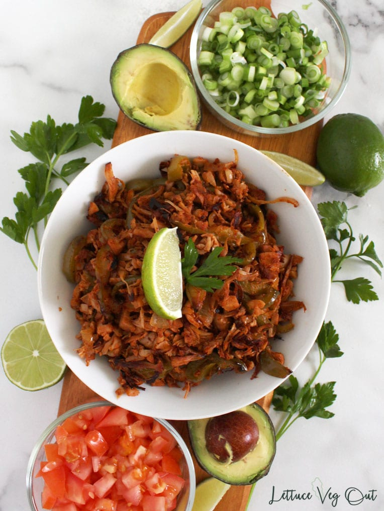 Top view of vegan fajita bowl on wooden board surrounded by fajitas toppings (tomato, green onion, avocado, cilantro, lime)