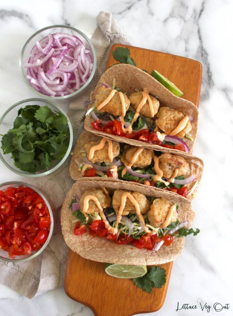 Top view of 3 vegan fish tacos covered in cream sauce with lime and cilantro holding the tortillas up and small glass jars of vegan taco ingredients to the side