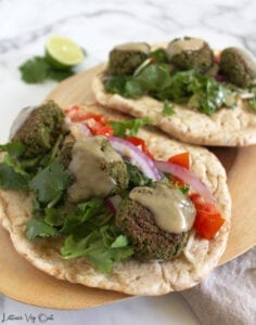 Two pita breads on wooden board, filled with edamame falafel, tahini sauce, tomato, red onion and lettuce