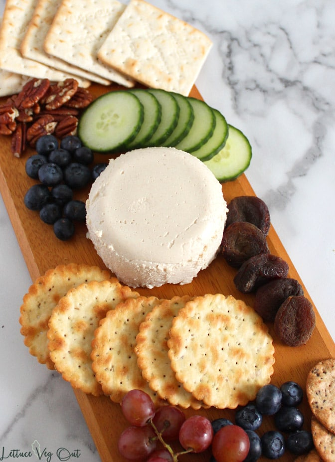 Close view of vegan goat cheese ball on long wooden board with cucumber slices, blueberries, grapes, pecans, dry apricots and crackers displayed around it