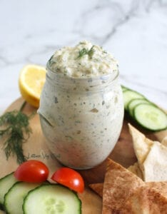 Vegan tzatziki sauce in glass jar on wooden board surrounded with pita bread triangles, cucumber slices, cherry tomatoes, lemon and dill