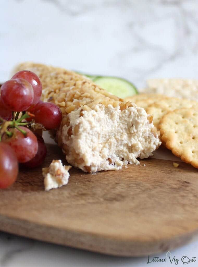 Vegan goat cheese log coated with crushed walnuts, on wooden board surrounded with crackers, red grapes and cucumber slices