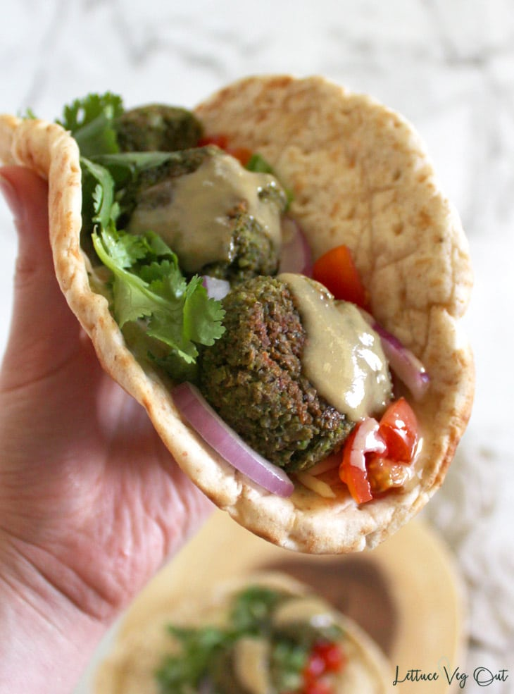 Hand holding up pita bread wrap filled with vegan edamame falafel, tahini sauce and vegetables; background shows blurred wrap on wooden board