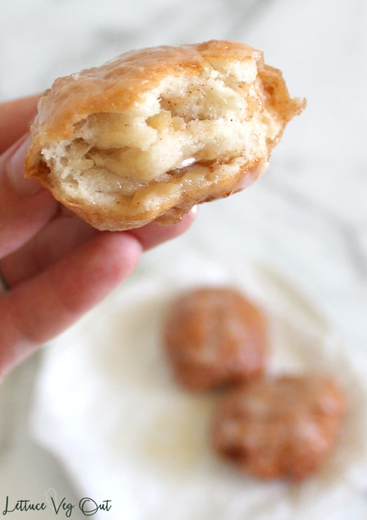 Hand holding half eaten fritter, showing layers inside the donut; above plate with two other donuts blurred out