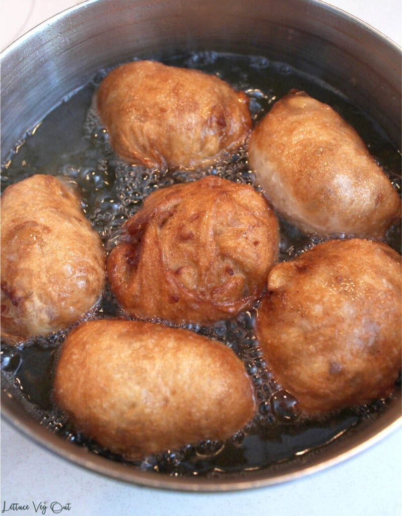 Metal pot filled with six fritters frying in oil (mostly cooked, golden brown donuts)