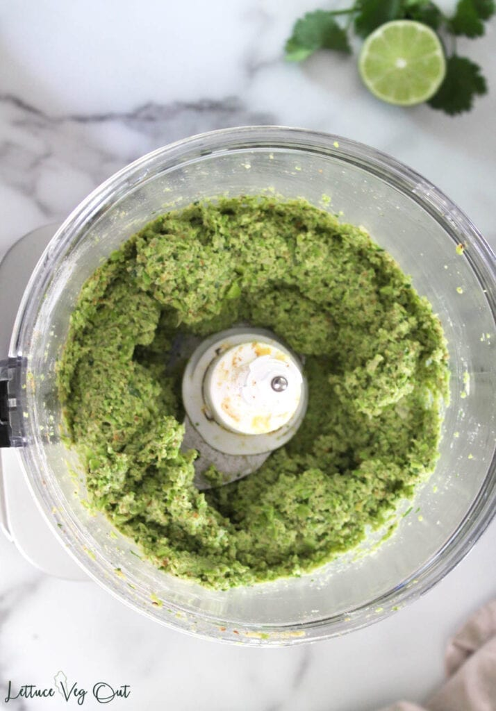 Food processor filled with green falafel mix with lime and cilantro garnish in back right corner