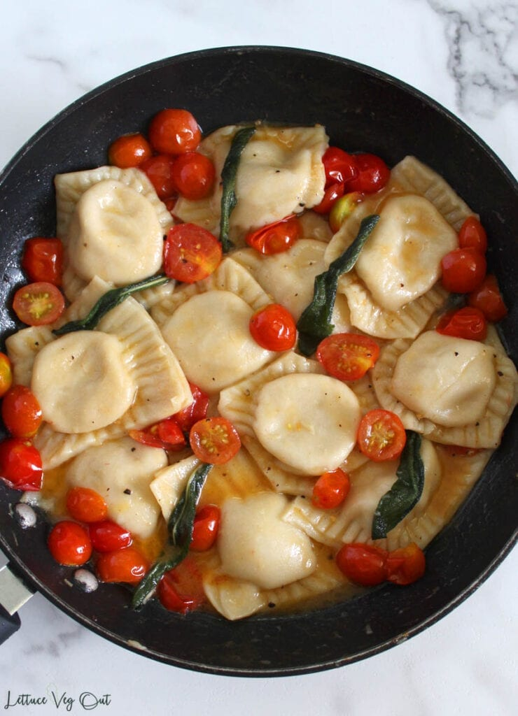 Large black pan on marble counter filled with square ravioli pasta and piece of cherry tomatoes and sage leaves
