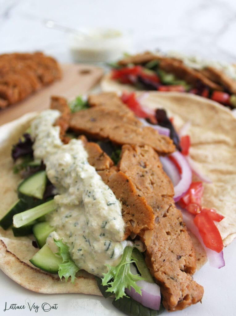 Pita bread filled with seitan gyro meat slices, cashew tzatziki sauce, cucumber, tomato, red onion and lettuce mix with blurred background of a second pita bread wrap, seitan gyro meat and sauce
