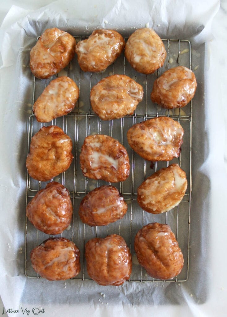 Top view of a large tray of glazed apple fritters set on a cooling rack above a parchment paper covered baking tray