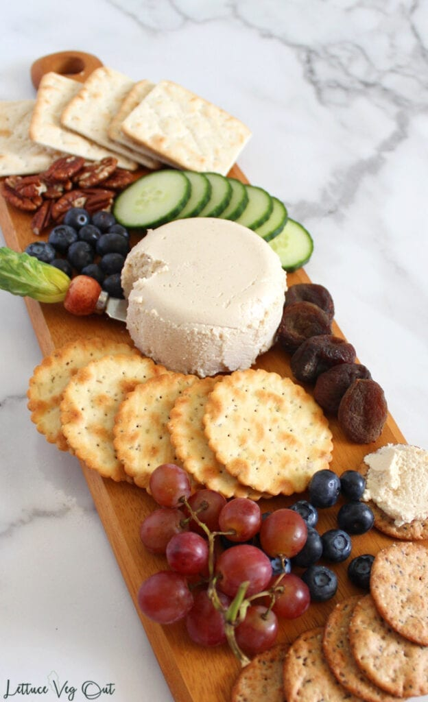 Long wood board of with ball of cashew goat cheese in center, small piece cut out from it with small knife; cheese surrounded by crackers, fruits and vegetables
