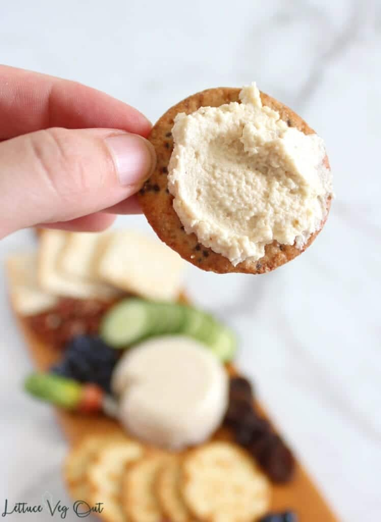Hand holding up small circular cracker covered with vegan chevre with blurred background of vegan cheese board (circular ball of cheese in center of long wooden board, surrounded with crackers, fruit and vegetables)