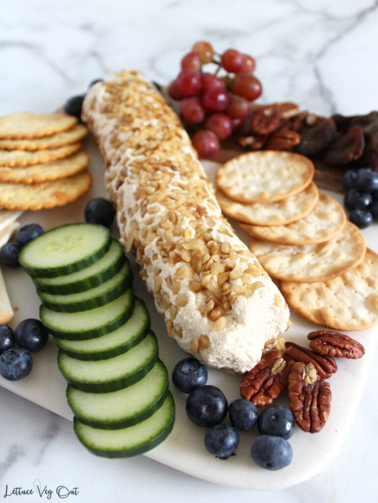 Square board with plant based goat cheese log coated in crushed walnuts in center, with crackers, cucumber slices, blueberries, pecans, and grapes surrounding the cheese