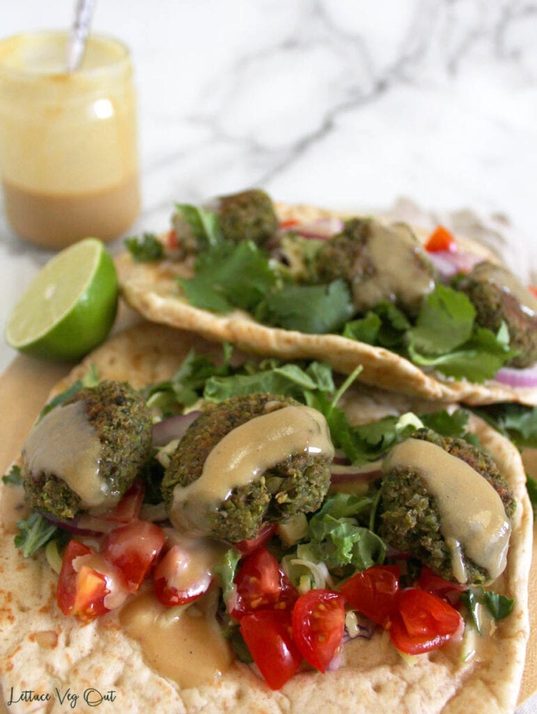 Two pita bread wraps on wooden board with half a lime between them and a glass jar of tahini sauce in back