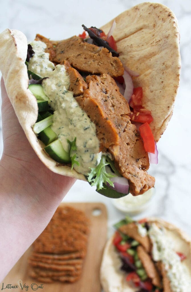 Hand holding up pita bread filled with vegan gyro ingredients (seitan, tzatziki, cucumber, tomato, red onion and lettuce mix) over blurred background of a second pita bread wrap and wooden board of extra vegan gyro meat