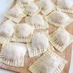 Raw ravioli on wooden board (square cut, with fork marks around edges of each piece)