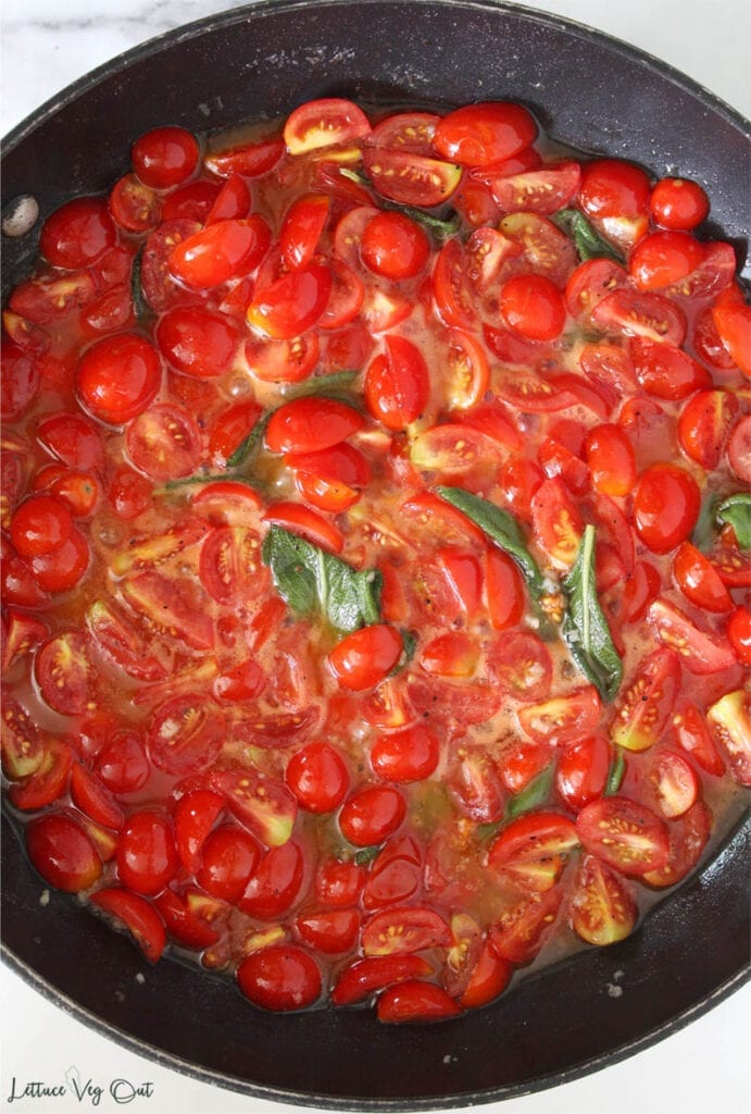 Large black pan filled with cooked cherry tomato, sage and vegan butter sauce