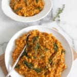 Two plates of vegan pumpkin risotto with the plate in front resting on small wooden board with a spoon in the risotto; springs of thyme between the bowls to the right