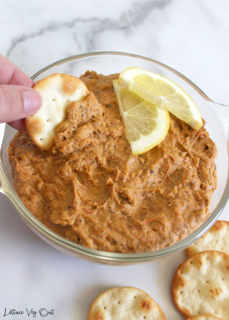 Hand dipping round pita bread cracker into butter bean dip in glass bowl topped with two half slices of lemon, surrounded by a few other crackers in bottom right corner; on white marble background