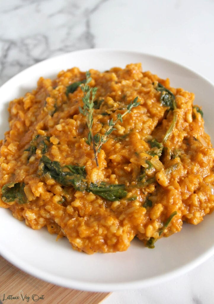 Close view of heaping plate of spinach and pumpkin risotto; white plate resting on small wooden board on top of marble background