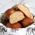 Bowl of whole wheat vegan dinner rolls with one cut in half