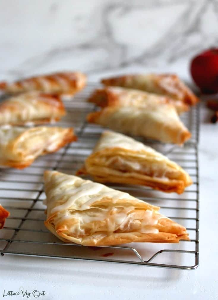 Image of vegan apple turnovers, baked and cooling on a metal rack with apples and cinnamon in background