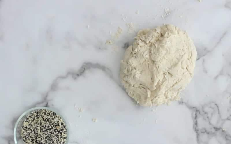 Image of vegan bagel dough with flour kneaded in with some additional flour on a marble background