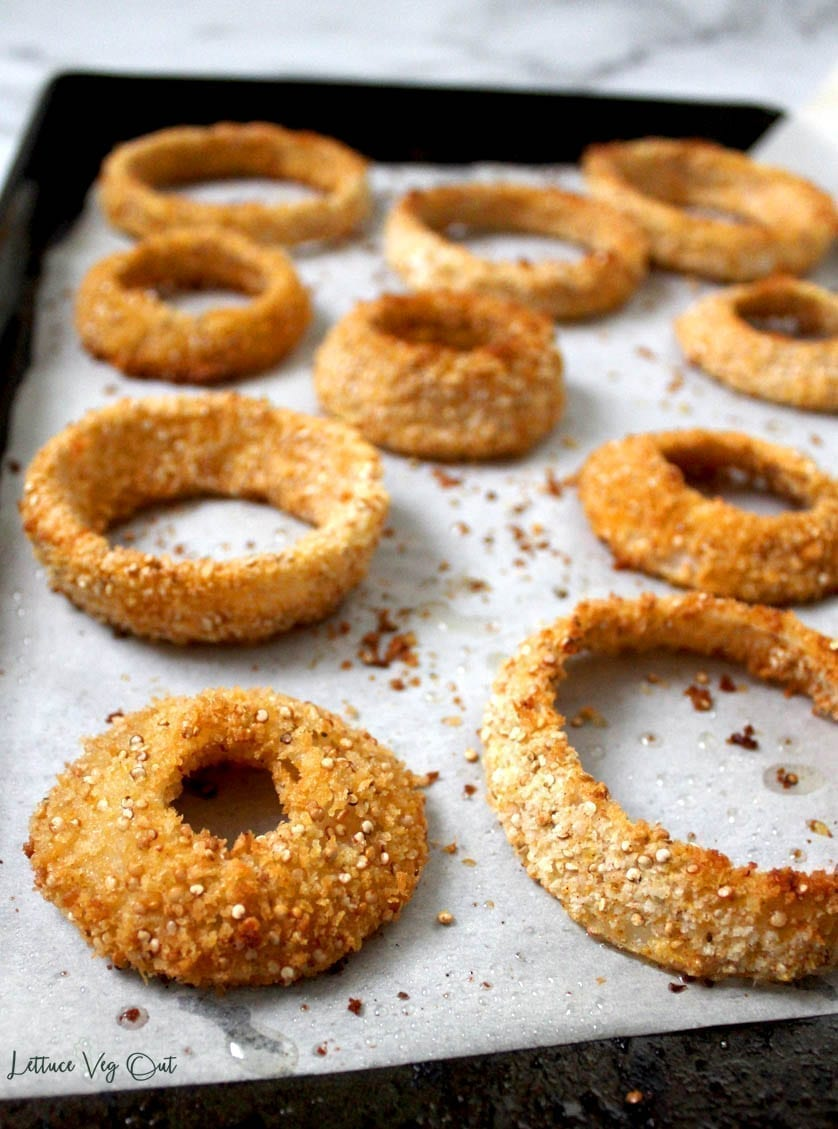 Image of vegan baked onion rings on a parchment paper-lined pan, showing the texture of quinoa breading