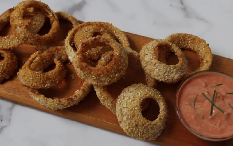 Image of wooden serving board covered in baked vegan onion rings with creamy sauce and green chives sprinkled on top.