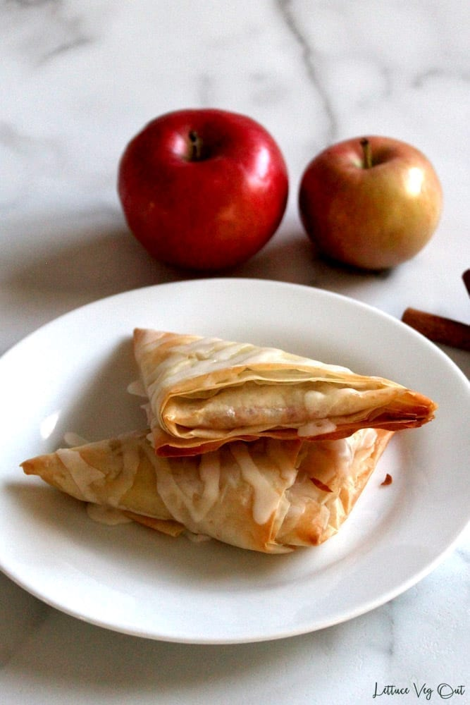 Image of two apple turnovers stacked on a white plate with two red apples in the background