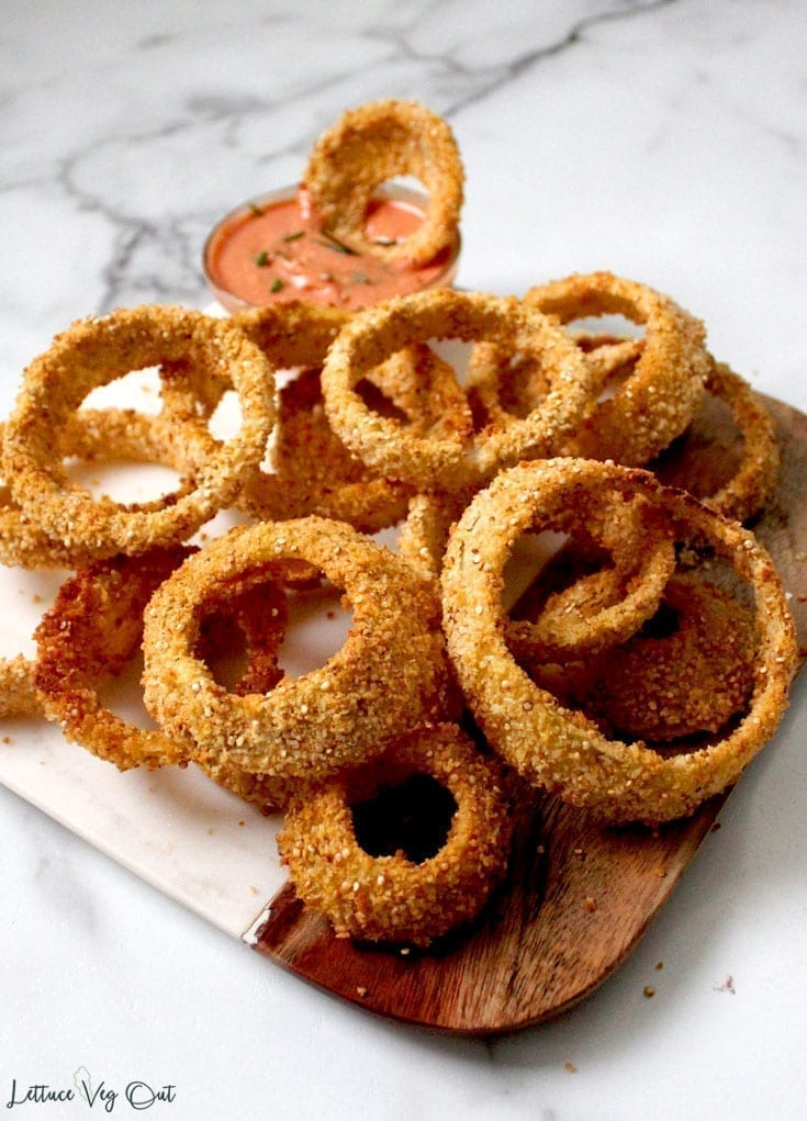 Image showing a plate full of quinoa coated vegan baked onion rings with creamy dip in background