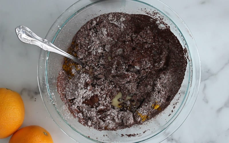 Wet and dry vegan chocolate orange icing ingredients in a glass bowl