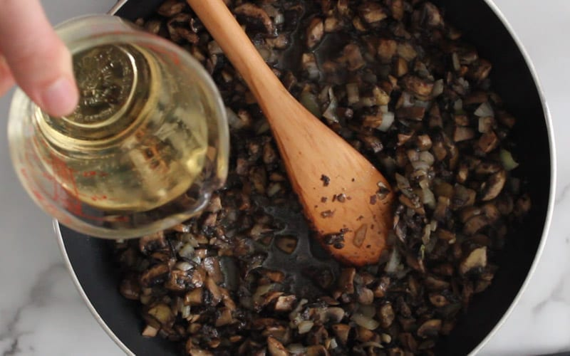 Add white wine to cooking mushrooms in fry pan