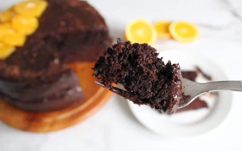 A bite of vegan chocolate orange cake on a fork with the rest of the cake and slice of cake in the background; out of focus