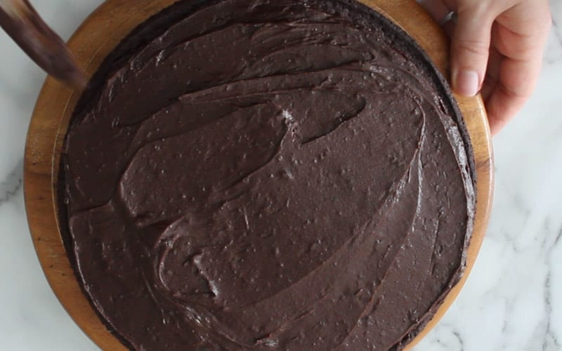 Spreading the eggless, dairy free chocolate orange icing onto a baked chocolate cake