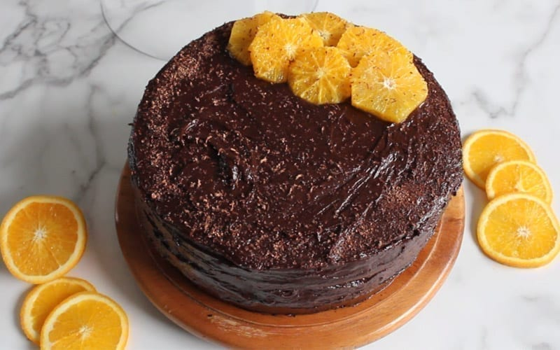 A whole vegan chocolate orange cake, served on a wooden cake plate. Topped with orange slices