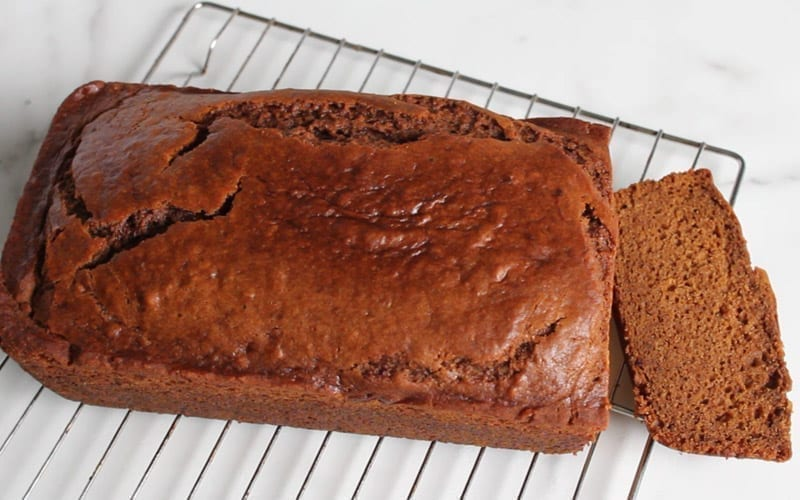 Baked vegan ginger loaf on a cooling rack after coming out of oven