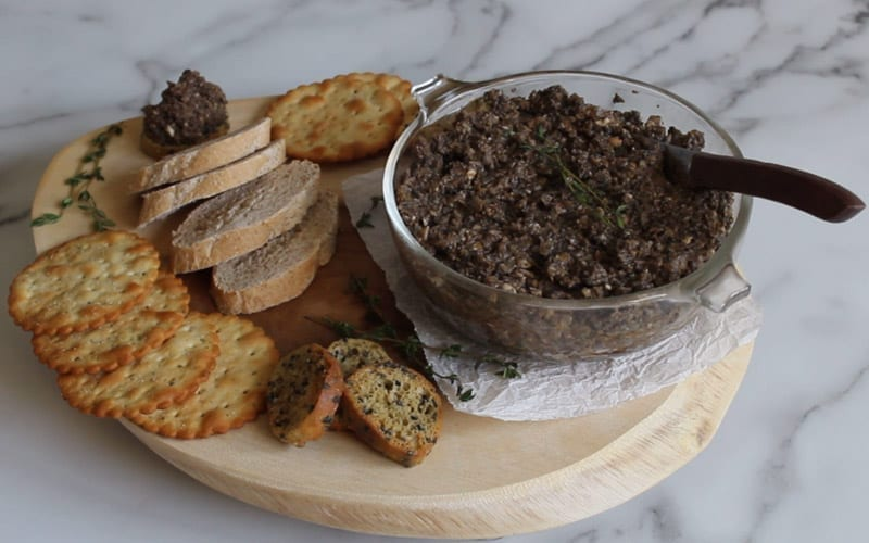 Bowl of mushroom pate on a serving board with crackers and baguette slices