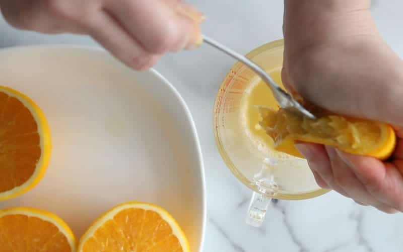 Juicing orange halves to add extra flavor into the eggless and dairy free chocolate orange cake