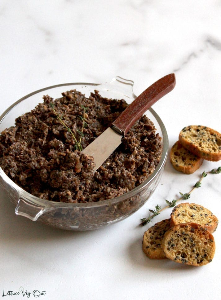 Vegan mushroom pate recipe in a glass bowl with small baguette crisps ready to scoop and serve