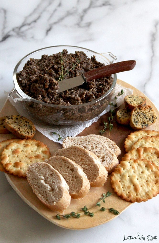Vegetarian mushroom pate with walnuts and lentils sitting in a glass dish on a serving board with baguette slices and crackers