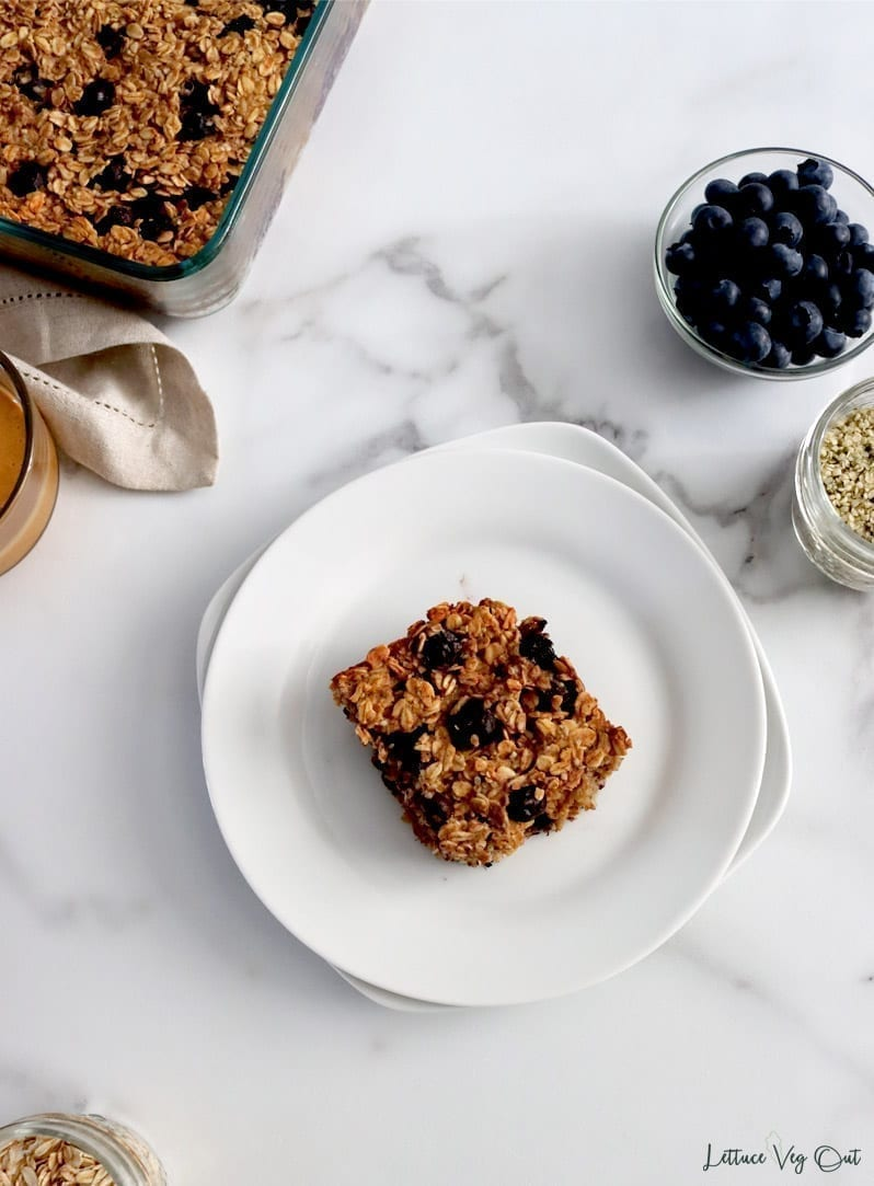 A served piece of blueberry baked oatmeal that contains vegan, plant-based ingredients. The piece is served on a white plate with space around it and individual ingredients in small glass dishes around the image's border