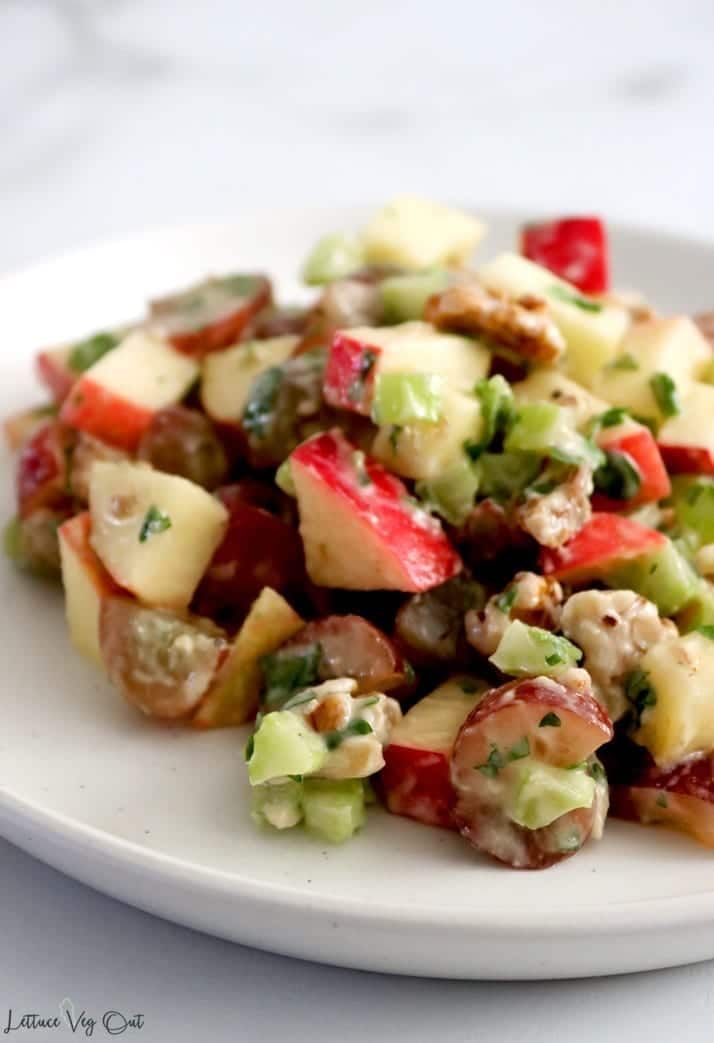 One plate with a heaping serving of Waldorf salad made from apple, walnuts and other vegan ingredients. The zoomed-in photo shows the creamy consistency of the salad dressing and equal amounts of all the plant-based ingredients.