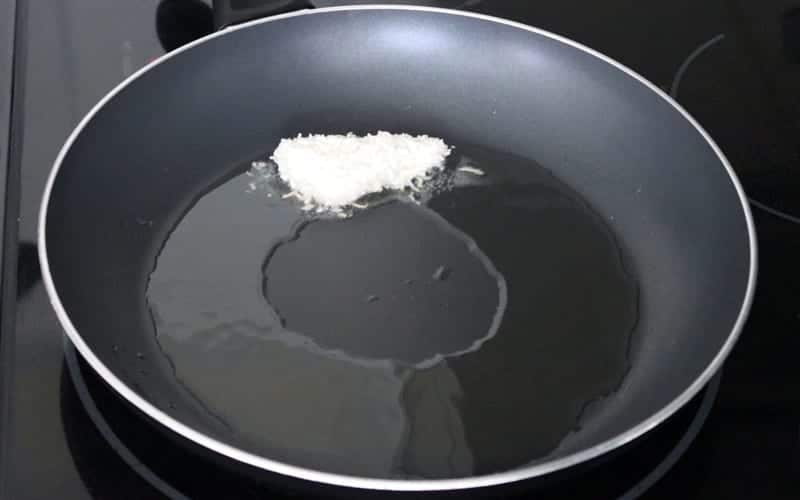 A single vegan coconut crusted tofu bite after breading, now in an oil-filled pan and starting to fry