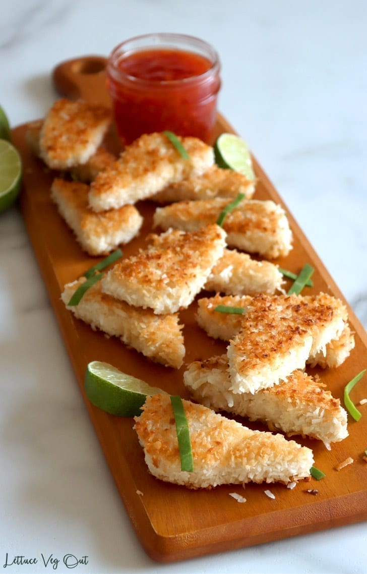 Crispy, golden-brown coconut crusted tofu pieces on a wooden serving board. Ready to eat and enjoy