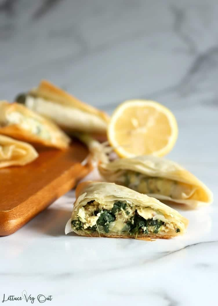 Vegan spanakopita sitting on a wooden serving board. A cut open triangle sits off to the side of the serving board with a half lemon behind it in the background