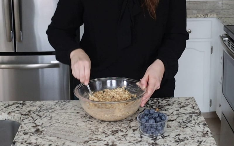 Mixed oatmeal in a large glass bowl with the only remaining ingredient, blueberries, sitting in a small glass dish to the side.