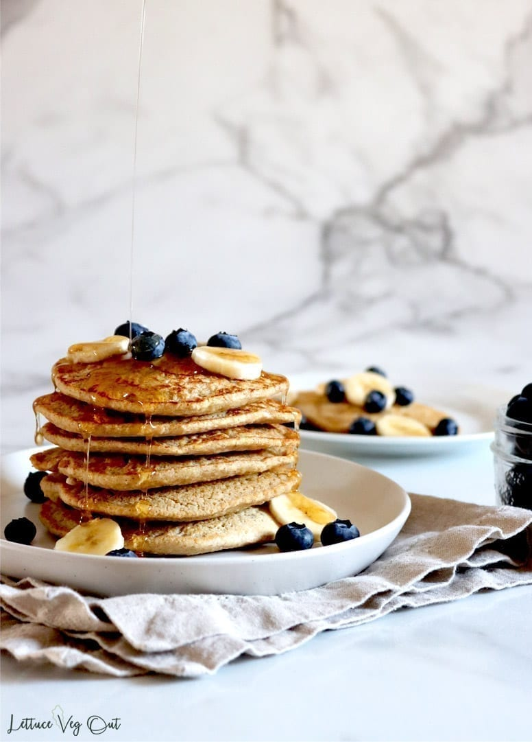 Two plates of vegan oat flour pancakes with blueberries, bananas and maple syrup. The closest plate of pancakes is stacked tall with syrup dripping from the top onto all other pancakes beneath it.