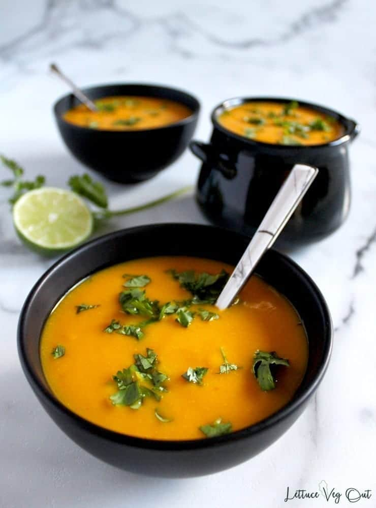 Three black bowls full of vegan spicy pumpkin soup, topped with finely chopped cilantro and ready to serve.