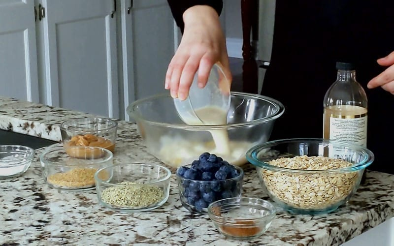 Pouring soy milk into banana in a large glass mixing bowl. Other remaining ingredients surround the glass mixing bowl waiting to be added into the oatmeal mixture